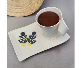 Black Swing Earrings with Yellow and White detail, placed next to a cup of coffee