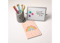 A pencil cup shaped like a cat with a rainbow notebook, and a whiteboard.