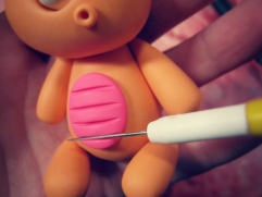 clay knife to cut pink polymer clay belly