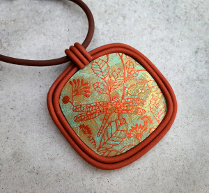 This mono printed silkscreen pendant has a bezel of 1:1 Souffle Cinnamon and Premo! Accents Bronze