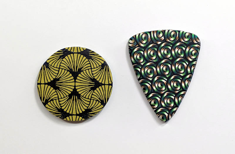 two pendants that demonstrate an unvarnished surface